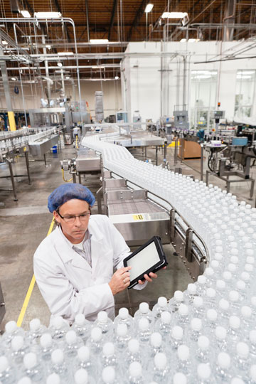 Bottling assembly line being overviewed by employee