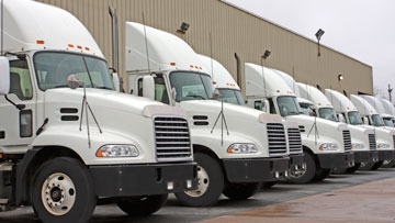White industry trucks parked in a line.
